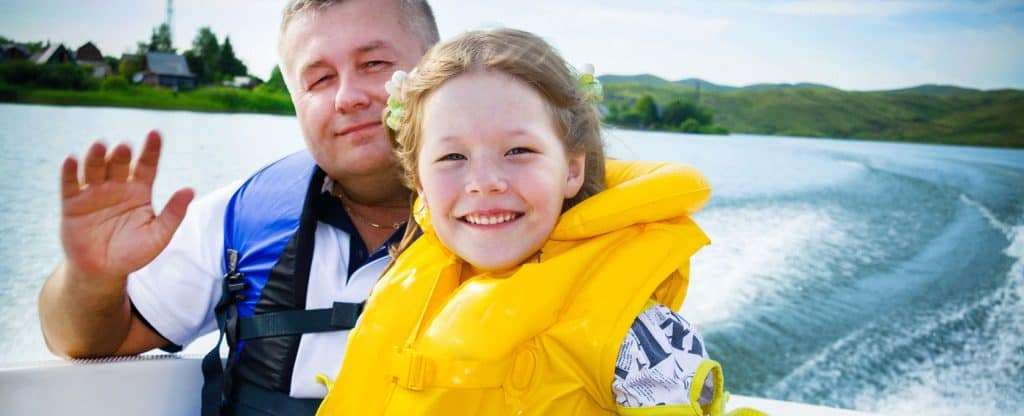 father and daughter with life jackets in boat