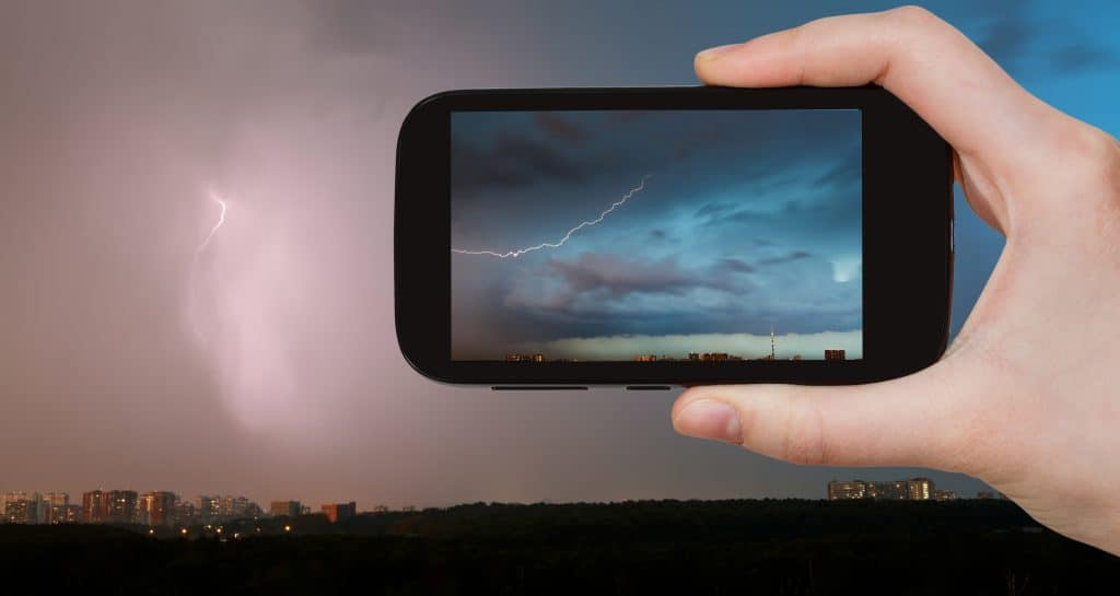 Smartphone taking a photo of a thunderstorm